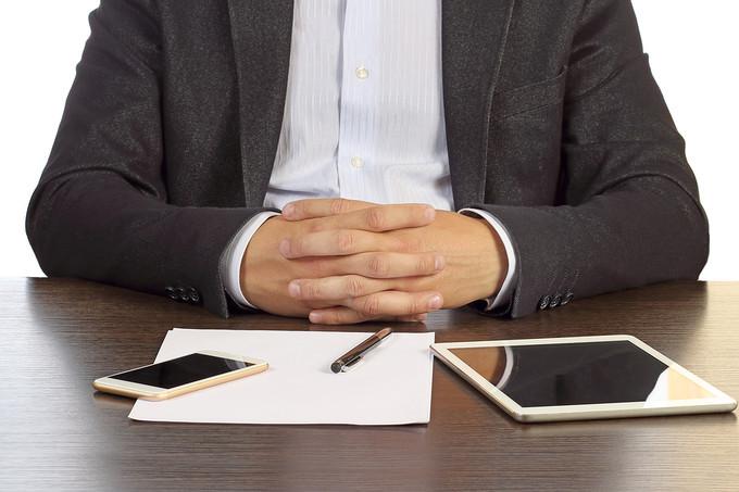 Businessman with Hands Folded on Desk