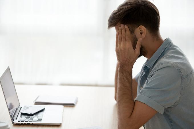Distressed Man Sitting at Desk